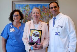 Jeri Davis, center, worked with Chicago-area artists to create a humorous coloring book for people who are experiencing cancer. She shared the book with Amy Forde, BSN, RN, OCN, an infusion nurse at the Northwestern Medicine Cancer Center in Warrenville (left), and oncologist Ahmad Zarzour, MD.